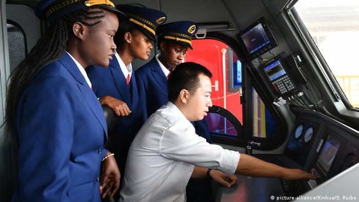 A Kenyan train crew watching the Chinese conductor aboard a Chinese-built train