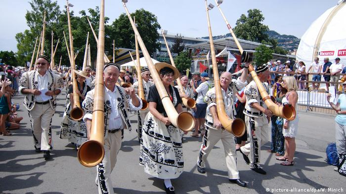 Participants gesture as they carry Alphorns at the festival