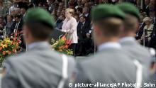 German Chancellor Angela Merkel, center, delivers a speech during an oath-taking ceremony of the German army at the Defence Ministry in Berlin, Germany