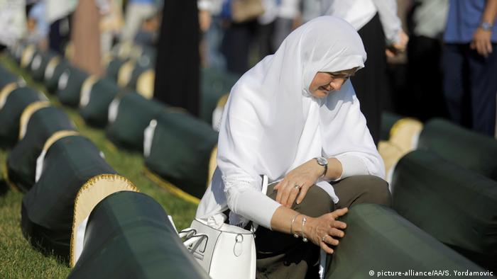 A women touches a coffin draped in green