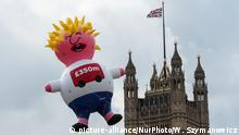 A Boris Johnson blimp flying next to the Houses of Parliament
