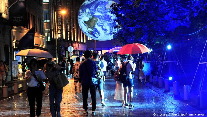 Visitors interact with GAIA, an artistic installation of glowing Earth in Shanghai (picture alliance/dpa/Jiang Xiaowei)