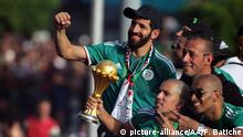 ALGIERS, ALGERIA - JULY 20: Sofiane Feghouli of Algeria holds the trophy during a welcoming at Houari Boumediene Airport, in Algiers, Algeria on July 20, 2019. Players of Algeria national football team, also known as 'Desert Warriors' are welcomed by tens of thousands Algerian fans at the airport. Algeria won their first Africa Cup of Nations (AFCON) title in 29 years, beating Senegal with 1-0. Farouk Batiche / Anadolu Agency   Keine Weitergabe an Wiederverkäufer.