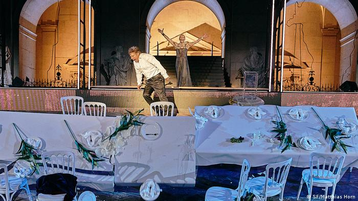 Man cries out in front of collapsed banquet tables, with a figure in a dress at stage rear, arms outstretched