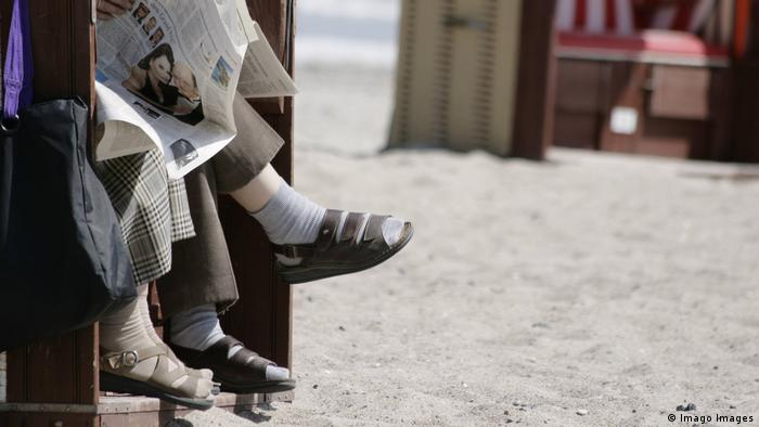 Feet of tourists wearing socks and sandals sitting in a beach basket