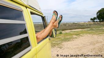 Eine Frau streckt die Beine aus dem Fenster ihres Wohnmobils