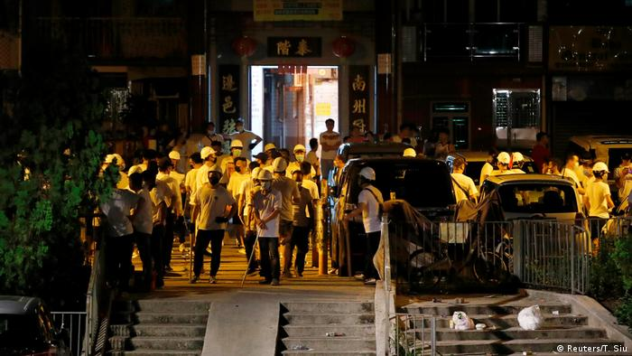 Men in white T-shirts with poles are seen in Yuen Long after attacking anti-extradition bill demonstrators (Reuters/T. Siu)
