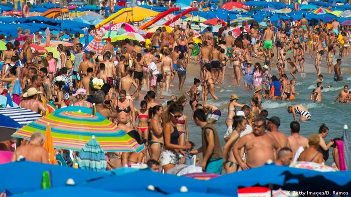 People sunbathe at Levante Beach in Benidorm, Spain