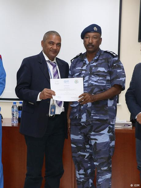 Officers in Sudanese police uniform receive certificates from Italian officials