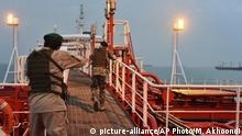 In this Sunday, July 21, 2019 photo, two armed members of Iran's Revolutionary Guard inspect the British-flagged oil tanker Stena Impero, which was seized in the Strait of Hormuz on Friday by the Guard, in the Iranian port of Bandar Abbas. Global stock markets were subdued Monday while the price of oil climbed as tensions in the Persian Gulf escalated after Iran's seizure of a British oil tanker on Friday. (Morteza Akhoondi/Mehr News Agency via AP) |
