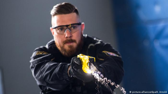 A German police officer using a taser in training