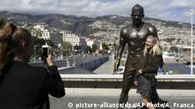 A tourist poses for a picture by a statue of Portuguese star soccer player Cristiano Ronaldo in Funchal, the capital of Madeira island, Portugal, Monday, March 27 2017. Ronaldo will play in his hometown of Funchal Tuesday when Portugal faces Sweden in a friendly soccer match. (AP Photo/Armando Franca) |