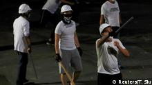 Men in white T-shirts with poles are seen in Yuen Long after attacked anti-extradition bill demonstrators at a train station, in Hong Kong, China July 22, 2019. REUTERS/Tyrone Siu
