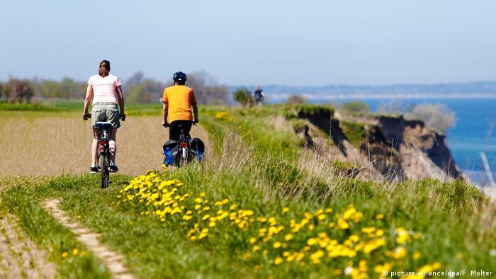 Una pareja recorre en bicicleta la costa del Mar Báltico. Uno de los lugares más frescos de Alemania durante la ola de calor que unos gozan y otros detestan. Algunos ya no vuelan a los concurridos destinos del Mediterráneo sino que prefieren quedarse y tomar la bicicleta para recorrer su ciudad, su región o medio país. Nada más sano, barato y ecológico que la bici.