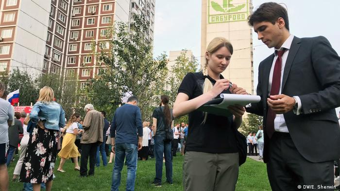Outside her apartment block, local resident Anna signs a petition opposing the construction of a highway