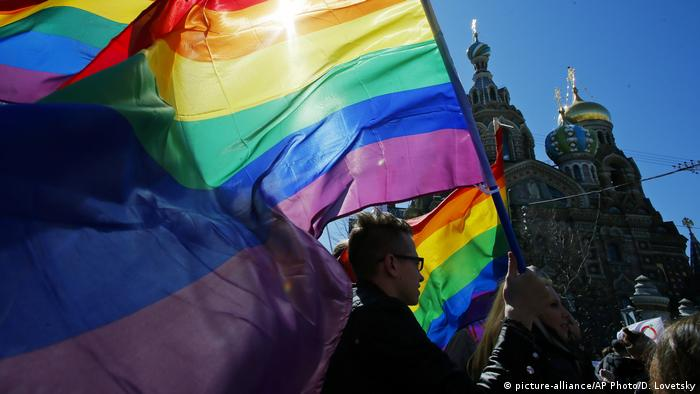 gay rights activists carry rainbow flags as they march during a May Day rally in St. Petersburg