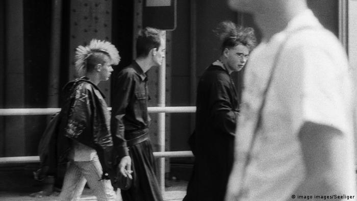 Ein Punk und zweu Grufties gehen auf der Straße
