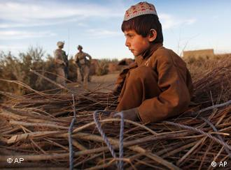 An Afghan boy sits on a pile of wood as he rides a donkey cart past two US Marines