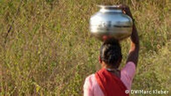 Woman carrying water canister on her head