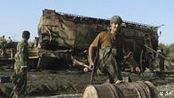 An Afghan soldier in front of the burned-out tanker after the airstrike