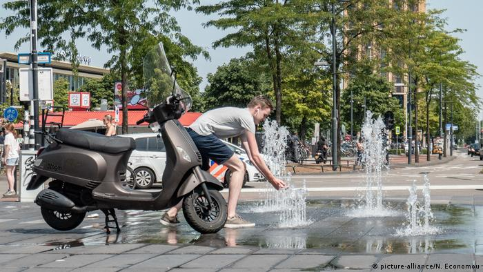 A man in Eindhoven grabs some water from a public fountain