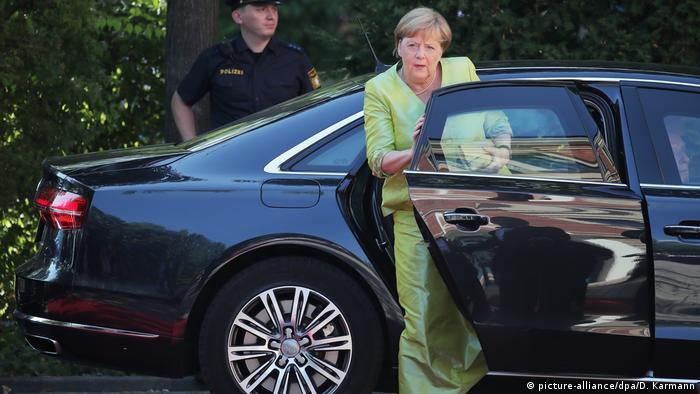 Angela Merkel gets out of a black car