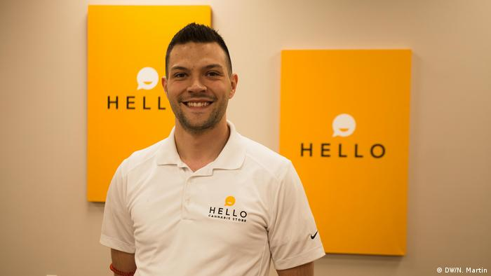 Cananbis tore owner Oliver Coppolino smiling in front of his company's logo — a smiley saying Hello.