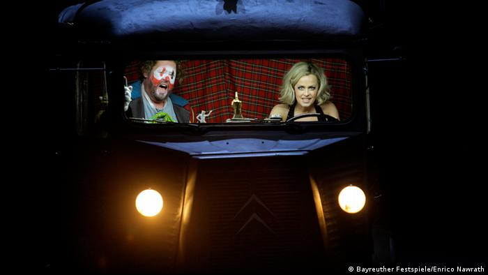 A clown and a blond woman in a black drerss drive in an old car