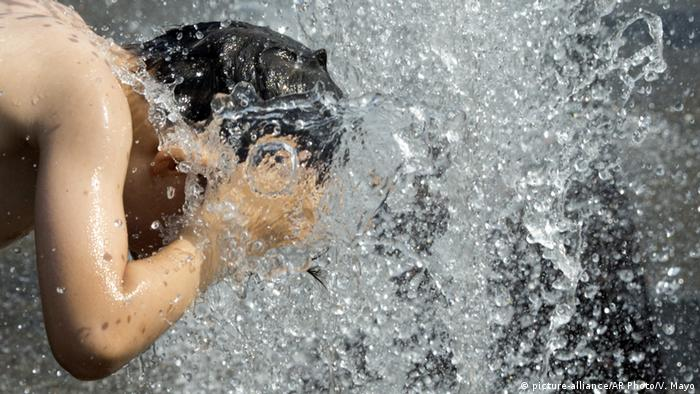A young boy cools his head off in a water fountain in Antwerp, Belgium