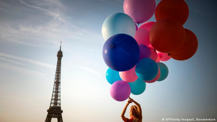 Woman holding a huge bunch of balloons in Paris with the Eiffel Tower in the background.