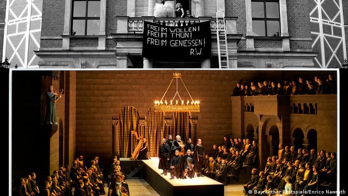 Mittelalterliche Szene unten, oben eine Videoeinspielung von Eindringlingen auf dem Balkon über dem Hauptportal des Bayreuther Festspielhauses
