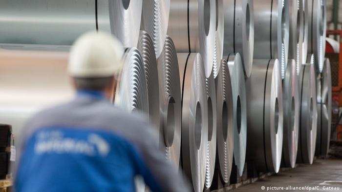 An employee rides past steel coils at Salzgitter AG