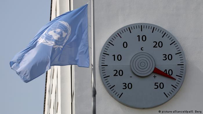A UN flag flies in front of a building in Bonn with a thermometer on it reading 42 degrees Celsius