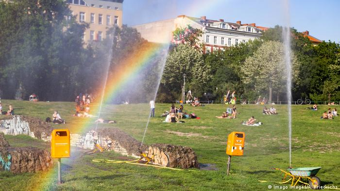 The sun's rays are broken by the spray of water from sprinklers, projecting a rainbow over people relaxing in a park (Imago Images/A. Friedrichs)