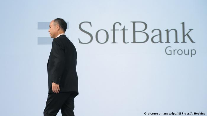 SoftBank logo in the background as CEO Masayoshi Son leaves a stage