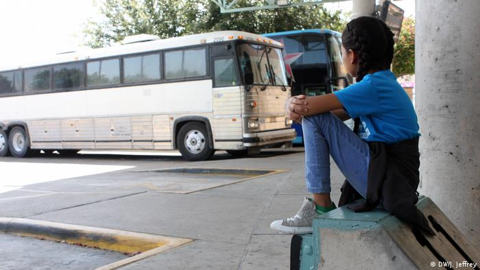 Nine-year-old Valeria from Honduras waits for the bus that will take her and her family north into the American interior