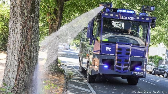 A water cannon truck in Wuppertal sprays a tree (picture alliance/dpa/C. Otte)