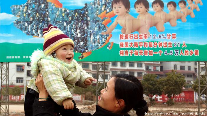 Una mujer china levanta a su hijo frente a una valla de propaganda de planificación familiar en el condado de Xinshao, provincia central de China, Hunan, febrero de 2005.