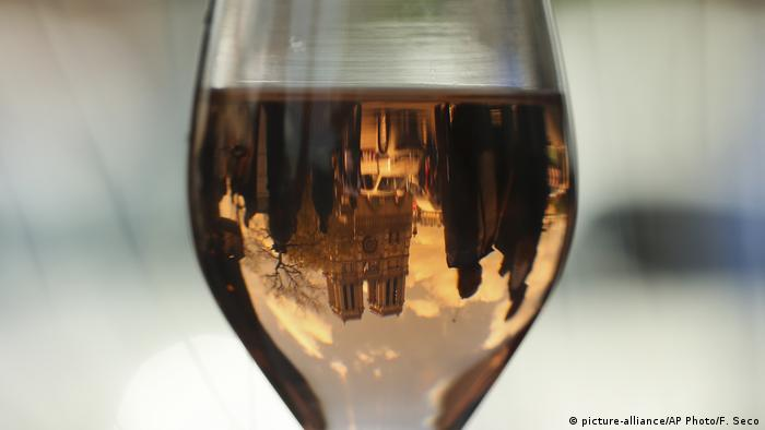 Notre Dame Cathedral is reflected in a wine glass in Paris, France