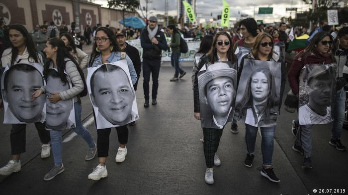 Demonstrators hold photos of murdered activists during a protest march in Bogota, Colombia (26.07.2019 picture-alliance/AP Photo/I. Valencia)