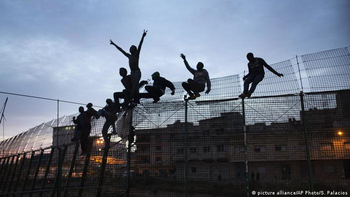 Migrants climb over Melilla border fence (picture alliance/AP Photo/S. Palacios)