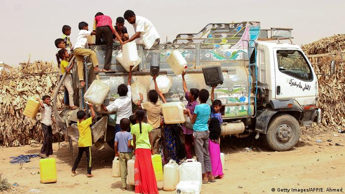 Displaced Yemenis from Hodeida fill jerrycans with water at a make-shift camp in the northern district of Abs in the country's Hajjah province, June 2019