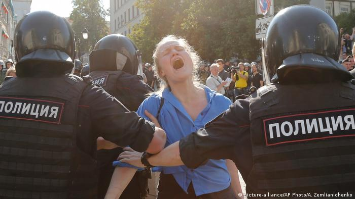 A protester in Moscow is held back by the police