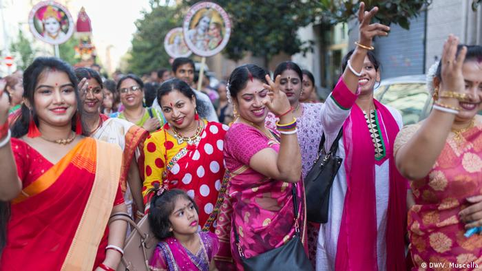 Indians and Bangladeshis taking part in a Hindu street procession in the heart of Torpignattara