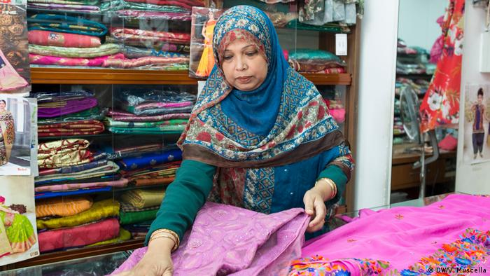 A Bangladeshi fashion shop owner arranging her products