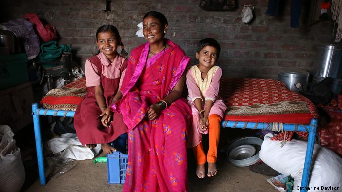 A woman sits on a bed with her two children