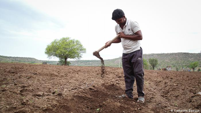A man stands in the field with a hoe