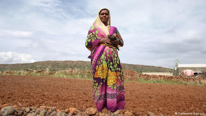 Pushpa Sadgar, 29, steht in einem bunten Sari auf dem Feld
