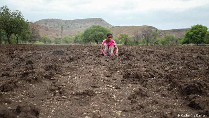 A woman sits working in a field