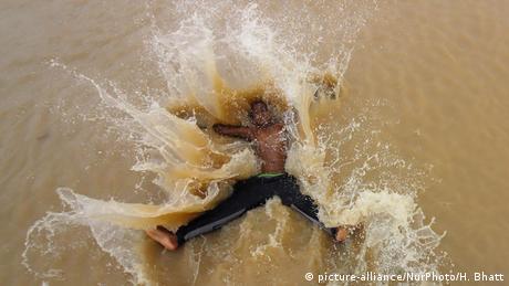 Dječak u indijskoj metropoli Mumbaji uživa u monsunskom rashlađenju